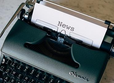 """A piece of paper with the word """"News"""" protrudes from a typewriter"""
